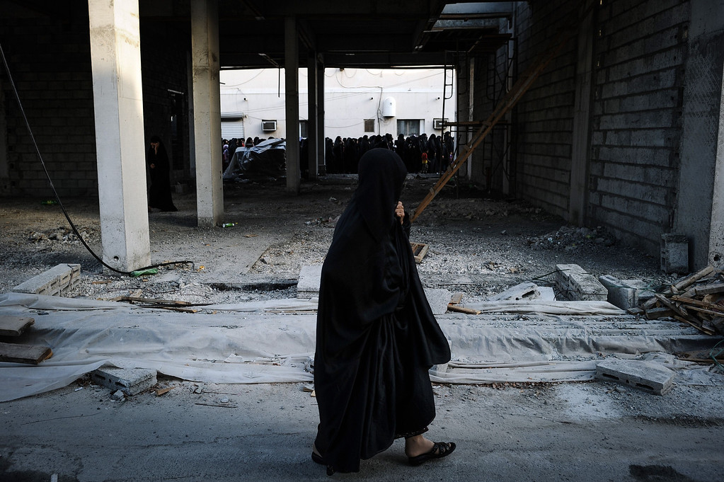 . A Bahraini women walks past the funeral of 10-year-old Ali Jaffer Habib, in the village of Malikiya, on August 10, 2013. Habib, according to his family, died after developing cancer due to the inhalation of tear gas fired by security forces earlier in the year. MOHAMMED AL-SHAIKH/AFP/Getty Images