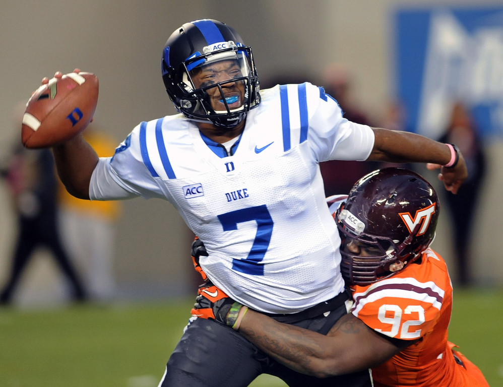. Duke quarterback Anthony Boone (7) looks to pass before Virginia Tech\'s Luther Maddy makes a sack during the second half of an NCAA college football game in Blacksburg, Va., Saturday Oct. 26, 2013. Duke won 13-10. (AP Photo/Don Petersen)