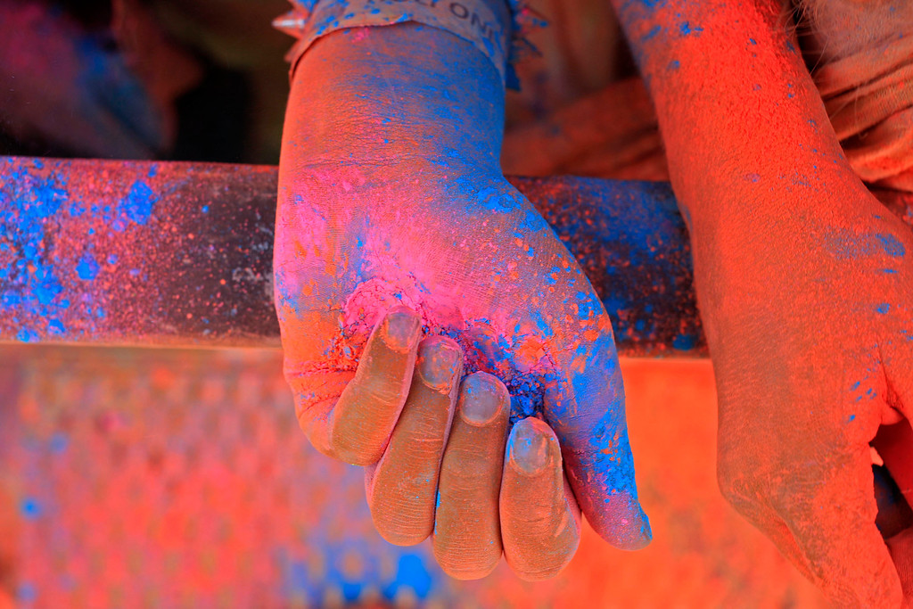 . A woman hands inside a cloud of paint powder next to her friend\'s during the holi one colour Festival held in the city of Cape Town , South Africa, Saturday, March 2, 2013. Thousands of people took part in the festival by throwing coloured paint powder at each other to express freedom and the colour of everyday life. (AP Photo/Schalk van Zuydam)