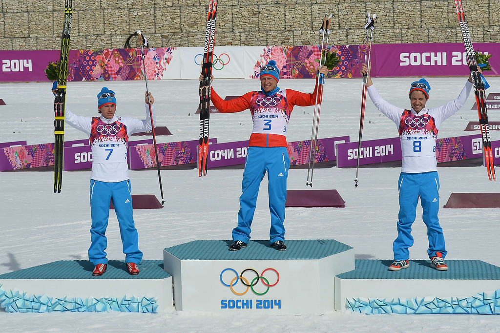 . Silver medalist Russia\'s Maxim Vylegzhanin (7) gold medalist Russia\'s Alexander Legkov (3) and Bronze medalist Russia\'s Ilia Chernousov (8) celebrate on the podium during the Men\'s Cross-Country Skiing 50km Mass Start Free Flower Ceremony at the Laura Cross-Country Ski and Biathlon Center during the Sochi Winter Olympics on February 23, 2014, in Rosa Khuto, near Sochi.  ALBERTO PIZZOLI/AFP/Getty Images