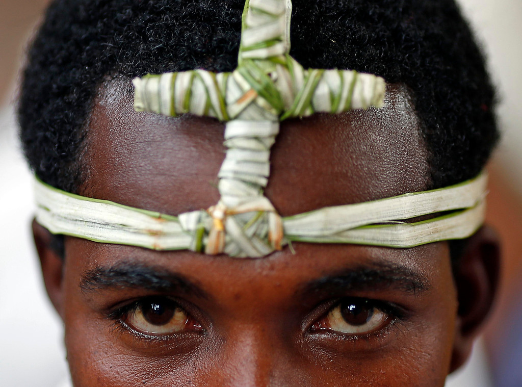. An Orthodox Christians wears a headband with a cross made from papyrus as he prays outside of one of 11 monolithic rock-cut churches, ahead of Orthodox Easter in Lalibela May 4, 2013.  REUTERS/ Goran Tomasevic