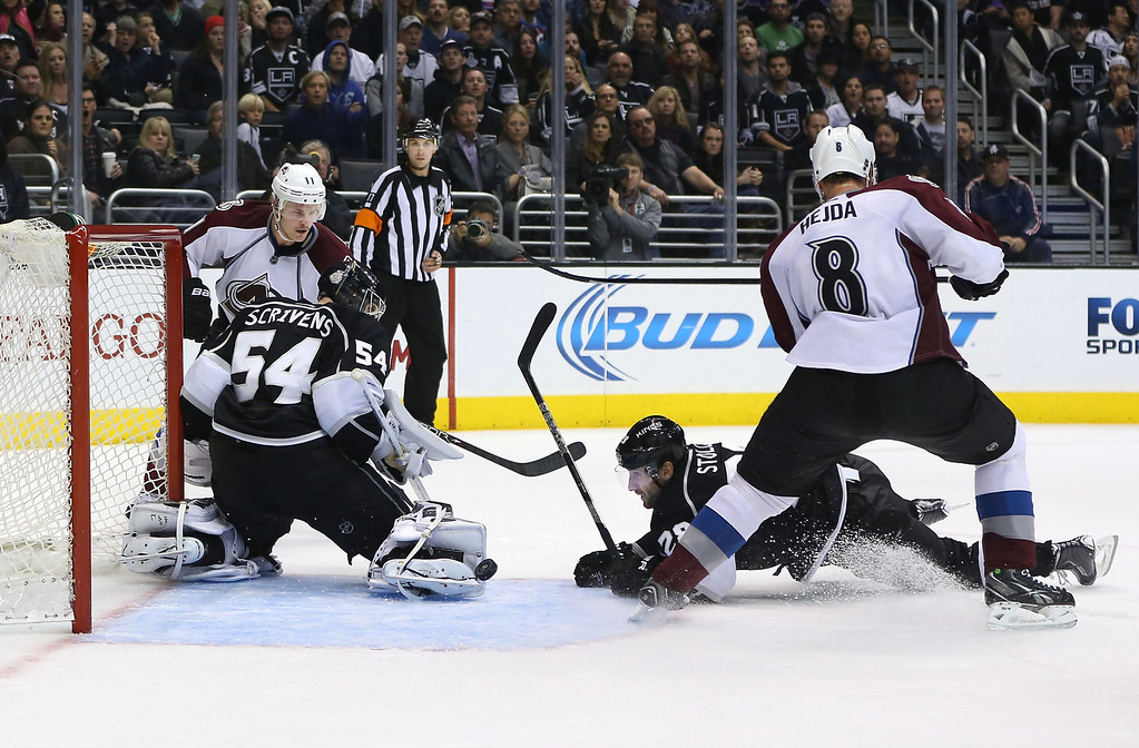. LOS ANGELES, CA - NOVEMBER 23:  Goaltender Ben Scrivens #54 of the Los Angeles Kings can\'t control the rebound of a shot by Jamie McGinn #11 of the Colorado Avalanche and deflects off Jarret Stoll #28 of the Los Angeles Kings into the net for a goal in overtime during the NHL game at Staples Center on November 23, 2013 in Los Angeles, California. The Avalanche defeated the Kings 1-0 in overtime. (Photo by Victor Decolongon/Getty Images)