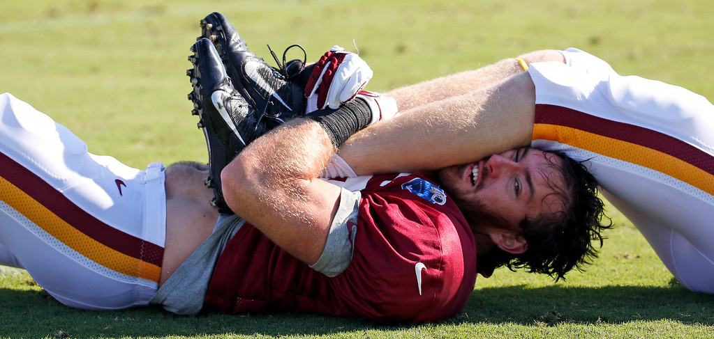 . Washington Redskins linebacker Gabe Miller lost his helmet, but hangs onto the legs of tight end Ted Bolser during practice at the team\'s NFL football training facility, Monday, July 28, 2014 in Richmond, Va. (AP Photo/Alex Brandon)