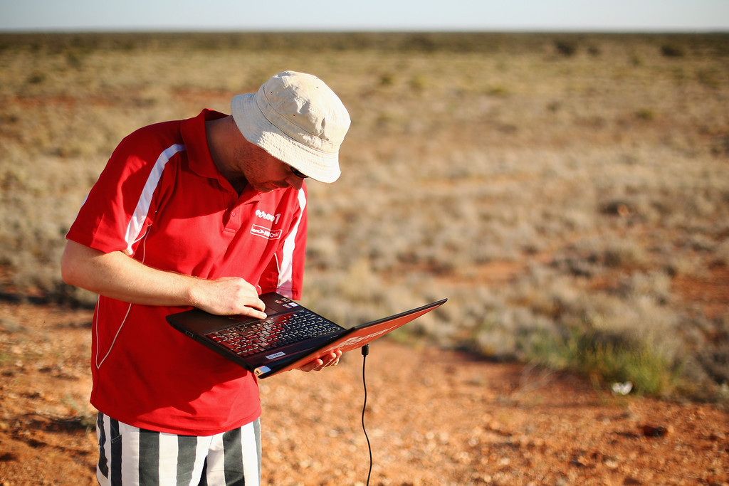 . ALICE SPRINGS, AUSTRALIA - OCTOBER 09:   Shane Hughes from Team Arrow, Associated with Queensland University of Technology in Australia works on a laptop as they prepare Arrow1 for racing on Day 4 on October 9, 2013 between Alice Springs and Kulgera, Australia. Over 25 teams from across the globe are competing in the 2013 World Solar Challenge - a 3000 km solar-powered vehicle race between Darwin and Adelaide. The race began on October 6th with the first car expected to cross the finish line on October 10th.  (Photo by Mark Kolbe/Getty Images)