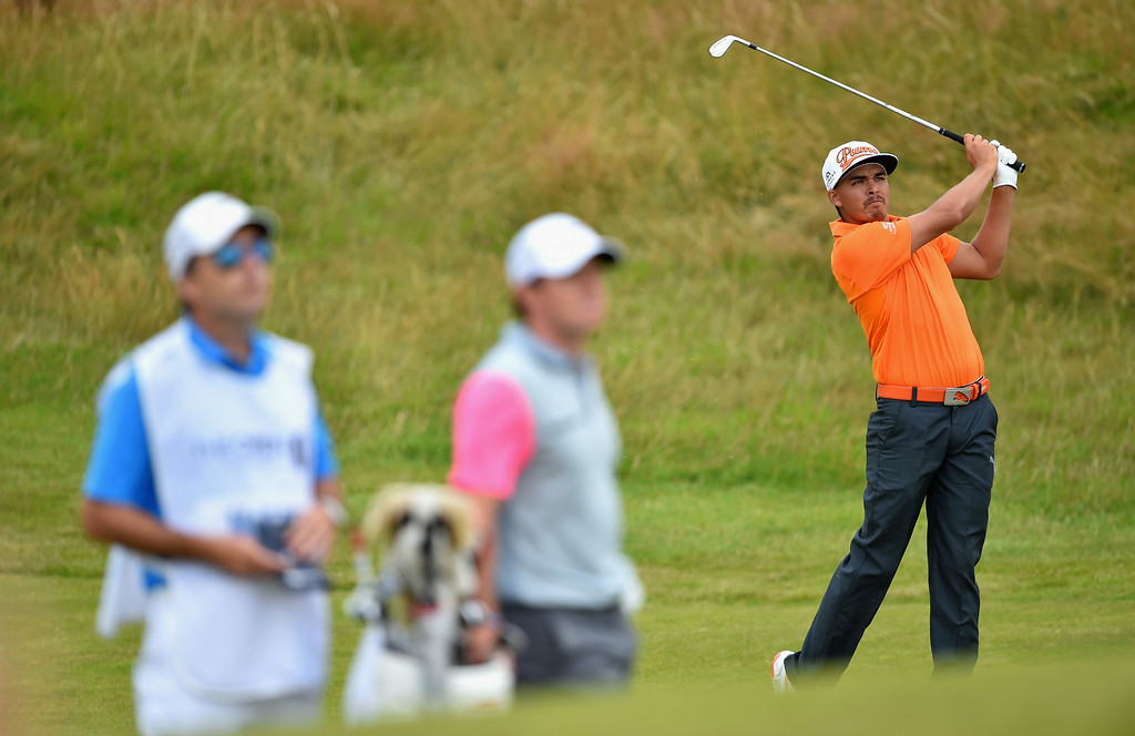 . Rickie Fowler of the United States hits his second shot on the 11th hole as Rory McIlroy of Northern Ireland and caddie J.P. Fitzgerald look on during the final round of The 143rd Open Championship at Royal Liverpool on July 20, 2014 in Hoylake, England.  (Photo by Stuart Franklin/Getty Images)