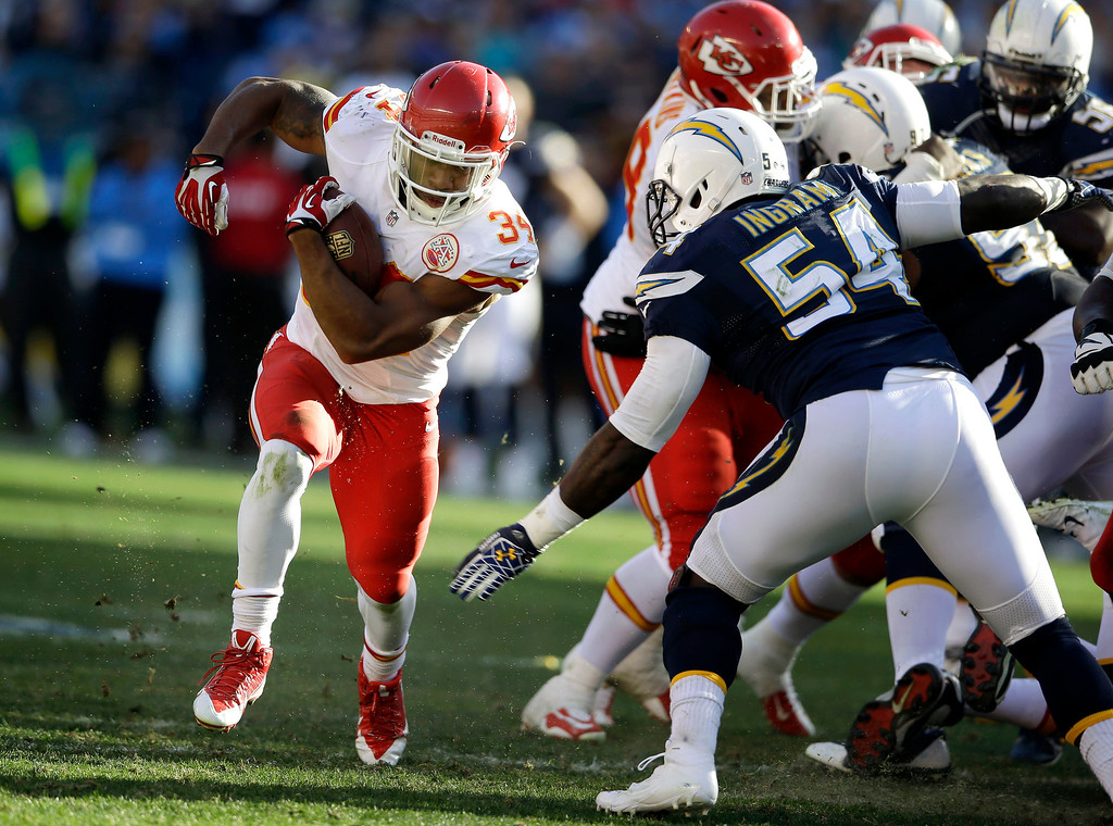 . Kansas City Chiefs running back Knile Davis, left, gets past the San Diego Chargers defense during the first half of  an NFL football game, Sunday, Dec. 29, 2013, in San Diego. (AP Photo/Lenny Ignelzi)