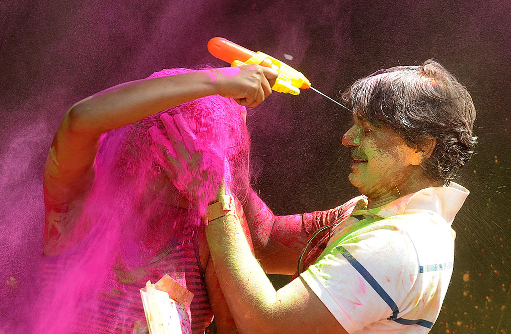 . Indian revelers play with colored powder during Holi celebrations in Hyderabad on March 17, 2014. Holi, also called the Festival of Colors, is a popular Hindu spring festival observed in India at the end of the winter season on the last full moon day of the lunar month. AFP PHOTO/Noah SEELAM/AFP/Getty Images