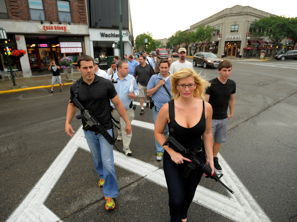 . In this June 11, 2012 file photo, Chris Combs, of Troy, left, and Stephanie Locke, of Clawson, cross the street in downtown Birmingham, Mich. while participating in a protest by gun enthusiasts.  The protest wass in support of eighteen-year-old Sean Michael Combs, of Troy, who was arrested in Birmingham while carrying a rifle. Combs was charged with brandishing a weapon, disturbing the peace, and obstructing a police officer.   (AP Photo/The Detroit News, David Guralnick, File)