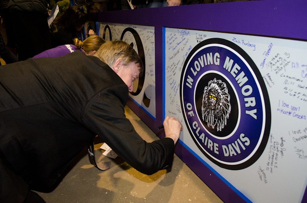 . Governor Hickenlooper signs the jump placard during the celebration of life service for Claire Davis, the Arapahoe High School shooting victim held at the National Western Stock Show Event Center in Denver, Co on January 1, 2014.   (Photo by Robert D. Tonsing/Courtesy of the Davis Family)