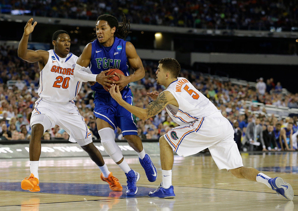 . Eddie Murray (23) is defended by Florida\'s Michael Frazier II (20) and Scottie Wilbekin (5) during the first half of a regional semifinal game in the NCAA college basketball tournament, Friday, March 29, 2013, in Arlington, Texas. (AP Photo/Tony Gutierrez)