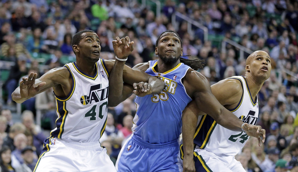 . Denver Nuggets\' Kenneth Faried, center, battles under the boards with Utah Jazz\'s Jeremy Evans (40) and Richard Jefferson (24) in the second quarter during an NBA basketball game, Monday, Jan. 13, 2014, in Salt Lake City. (AP Photo/Rick Bowmer)