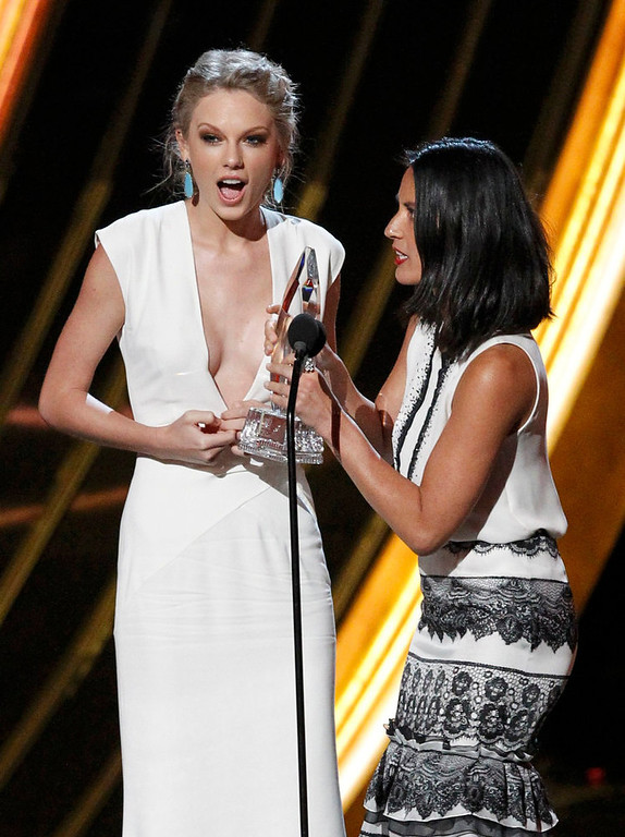 ". Taylor Swift (L) accepts the award for ""Favorite Country Artist\"" by presenter Olivia Munn at the 2013 People\'s Choice Awards in Los Angeles, January 9, 2013.   REUTERS/Mario Anzuoni"