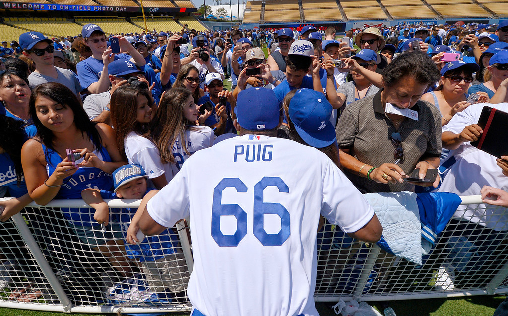 . Los Angeles Dodgers\' Yasiel Puig poses for pictures during On-Field Photo Day prior to the Dodgers\' baseball game against the Colorado Rockies, Saturday, July 13, 2013 in Los Angeles.  (AP Photo/Mark J. Terrill)