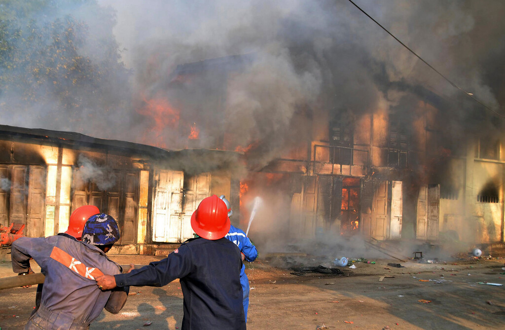 . Myanmar fire fighters put out fires in a burning building following ethnic unrest between Buddhists and Muslims in Meikhtila, Mandalay division, about 550 kilometers (340 miles) north of Yangon, Myanmar, Friday, March. 22, 2013. (AP Photo/Khin Maung Win)
