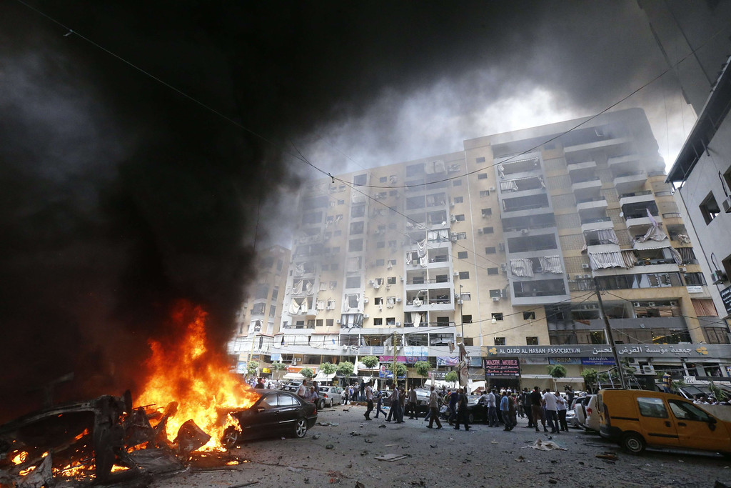 . Firefighters and residents gather at the site of an explosion in Beirut\'s southern suburb neighbourhood of Bir al-Abed on July 9, 2013.  AFP PHOTO/STR-/AFP/Getty Images