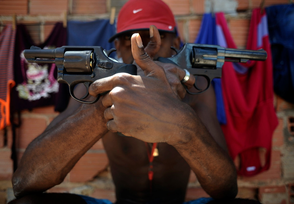 . A Brazilian drug gang member nicknamed Pilintra, 26, poses with a gun atop a hill overlooking a slum in Salvador, Bahia State, April 11, 2013. One of Brazil\'s main tourist destinations and a 2014 World Cup host city, Salvador suffers from an unprecedented wave of violence with an increase of over 250% in the murder rate, according to the Brazilian Center for Latin American Studies (CEBELA). Picture taken April 11, 2013.  REUTERS/Lunae Parracho