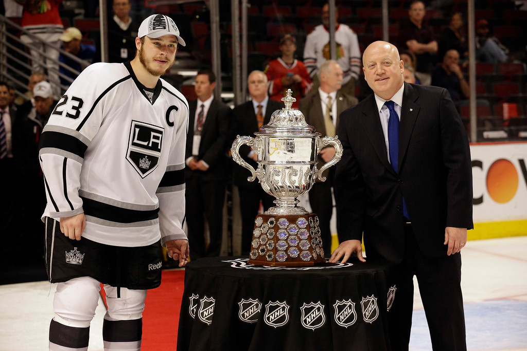 . Los Angeles Kings right wing Dustin Brown (23) poses with NFL deputy commissioner Bill Daly with the Clarence S. Campbell Bowl after Los Angeles Kings defeated Chicago Blackhawks 5-4 in the overtime period in Game 7 of the Western Conference finals in the NHL hockey Stanley Cup playoffs Sunday, June 1, 2014, in Chicago. (AP Photo/Nam Y. Huh)