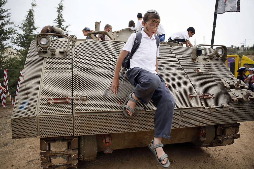 . An Israeli boy jumps from an Armoured Personnel Carrier during a traditional military weapon display to mark the 66th anniversary of Israel\'s Independence at the West Bank settlement of Efrat on May 6, 2014 near the biblical city of Bethlehem. Israelis are marking Independence Day, celebrating the 66th year since the founding of the Jewish State in 1948 according to the Jewish calendar. AFP PHOTO/GALI TIBBON