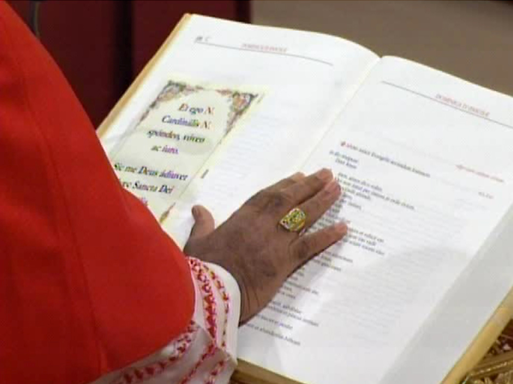 ". In this image taken from video provided by CTV, a cardinal places his hands on the Gospel to ""promise pledge and swear\"" to keep the oath of secrecy after entering the Sistine Chapel in Vatican City for the conclave to elect the next pope Tuesday, March 12, 2013. (AP Photo/CTV)"