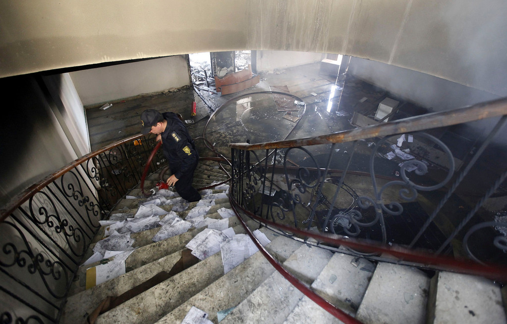 ". A firefighter walks up the stairs at the headquarters of the Egyptian Soccer Federation after Al Ahly fans, also known as ""Ultras\"" set it on fire following a court verdict, in Cairo March 9, 2013.  REUTERS/Amr Abdallah Dalsh"