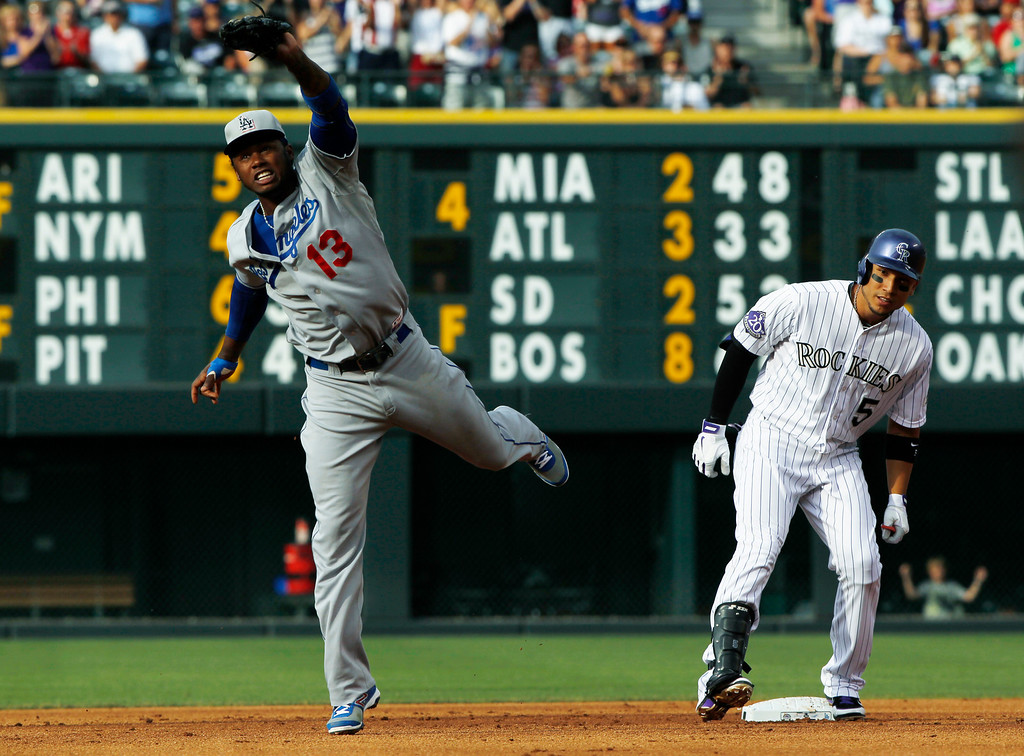 . Los Angeles Dodgers shortstop Hanley Ramirez, left, jumps to field a throw from the outfield as Colorado Rockies\' Carlos Gonzalez, right, pulls into second base with an RBI-double in the first inning of a baseball game in Denver, Thursday, July 4, 2013. (AP Photo/David Zalubowski)