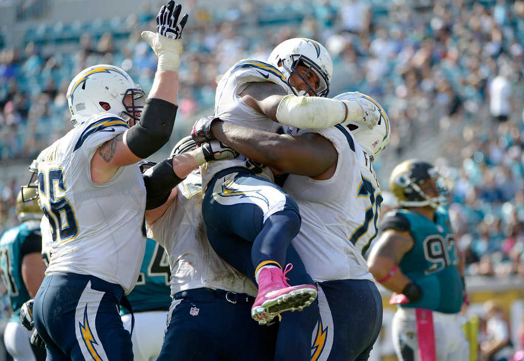. San Diego Chargers running back Ryan Mathews, center, is mobbed by teammates after scoring a touchdown on a 3-yard run against the Jacksonville Jaguars during the second half of an NFL football game in Jacksonville, Fla., Sunday, Oct. 20, 2013.(AP Photo/Phelan M. Ebenhack)