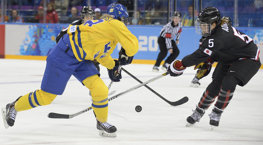 . Sweden\'s Anna Borgqvist (L) vies with Japan\'s Kanae Aoki during the Women\'s Ice Hockey Group B match Sweden vs Japan at the Shayba Arena during the Sochi Winter Olympics on February 9, 2014.   ALEXANDER NEMENOV/AFP/Getty Images