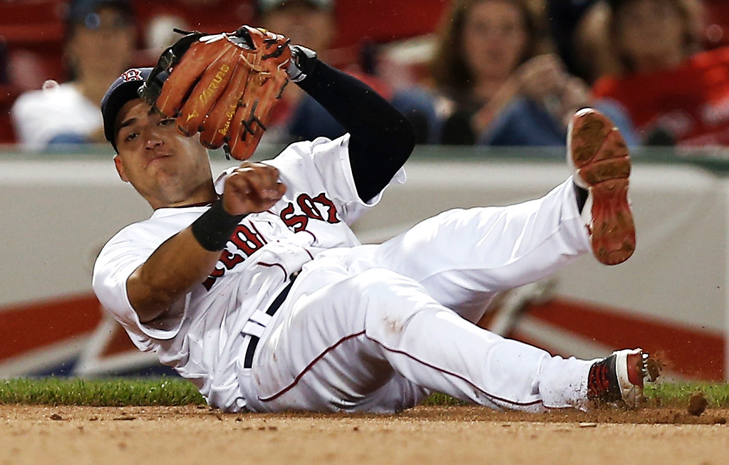 . Boston Red Sox third baseman Jose Iglesias falls while trying to throw out Colorado Rockies\' DJ LeMahieu, who reached on an error by Iglesias during the ninth inning of Boston\'s 11-4 win in a baseball game at Fenway Park in Boston on Tuesday, June 25, 2013. (AP Photo/Winslow Townson)