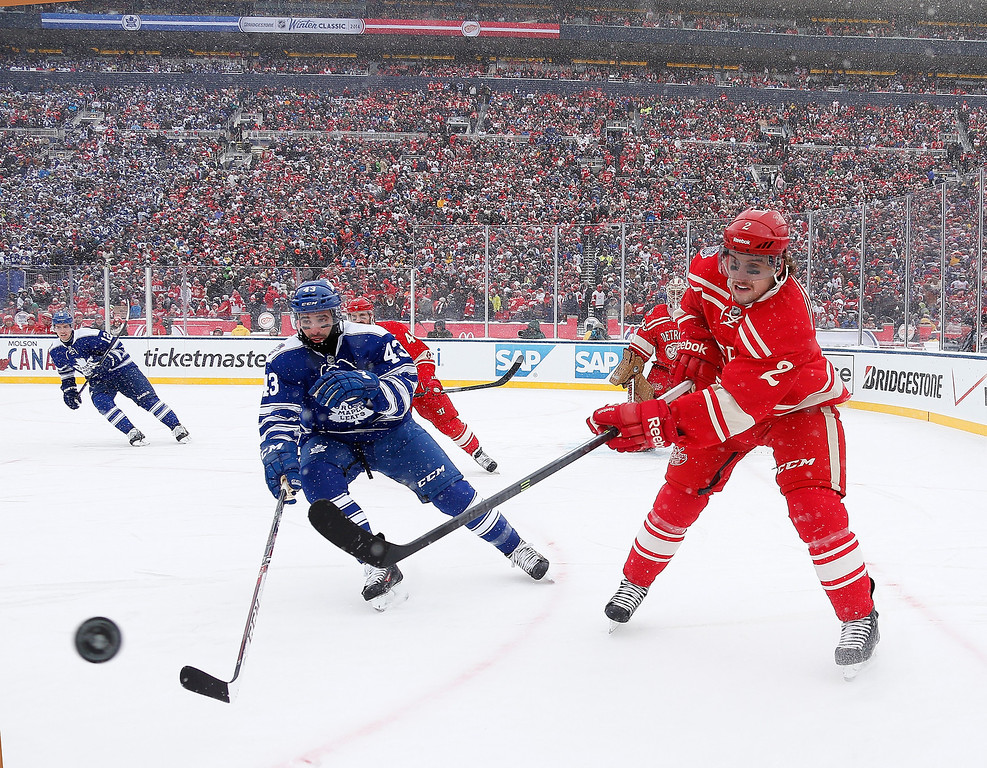 . Brendan Smith #2 of the Detroit Red Wings fires the puck while Nazem Kadri #43 of the Toronto Maple Leafs closes in during the first period of the 2014 Bridgestone NHL Winter Classic at Michigan Stadium on January 1, 2014 in Ann Arbor, Michigan. (Photo by Gregory Shamus/Getty Images)