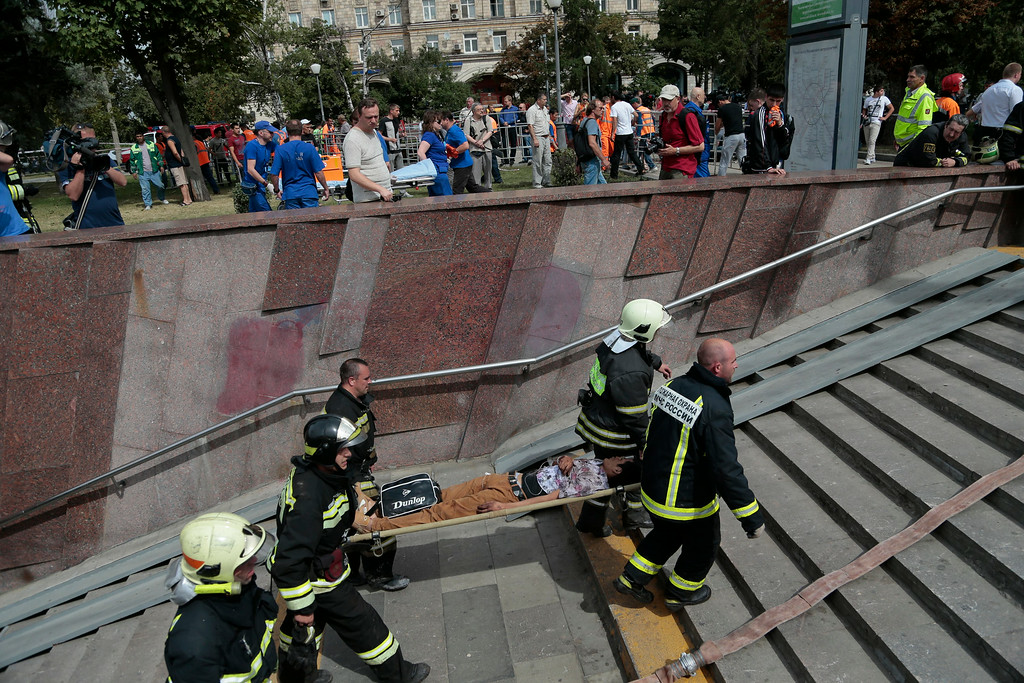 . Emergency Ministry firefighters carry an injured man out from a subway station after a rush-hour subway train derailment in Moscow, Russia, on Tuesday, July 15, 2014.  (AP Photo/Ivan Sekretarev)