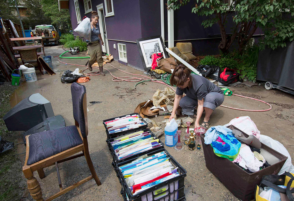 . Elain Schmidt (R) and Stephanie Martin help move house articles from a flooded house in the Elbow Park area of Calgary, Alberta June 22, 2013. REUTERS/Todd Korol