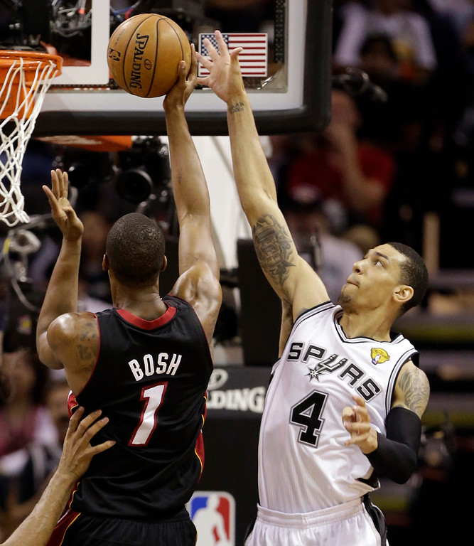 . Miami Heat\'s Chris Bosh (1) shoots as San Antonio Spurs\' Danny Green (4) defends during the first half at Game 4 of the NBA Finals basketball series, Thursday, June 13, 2013, in San Antonio. (AP Photo/Eric Gay)