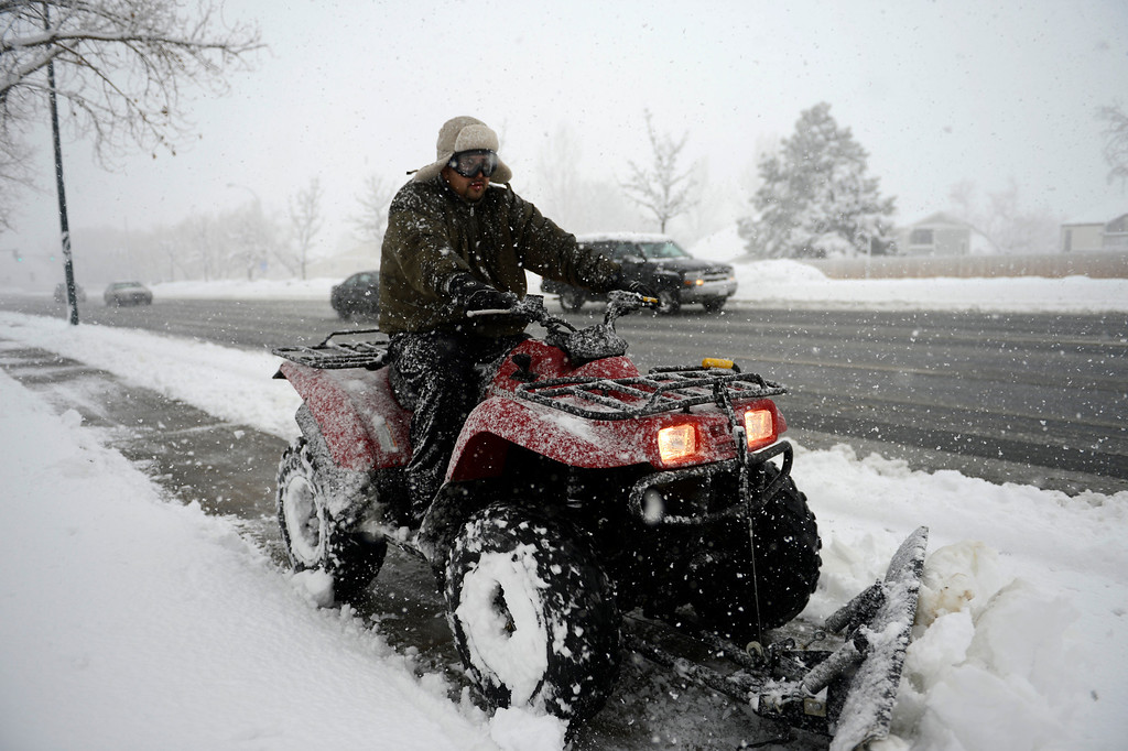 . ARVADA, CO. - MARCH 09: A worker plows the sidewalk on 88th in Arvada as the snow continues to fall March 09, 2013. Arvada, Colorado. (Photo By Joe Amon/The Denver Post)