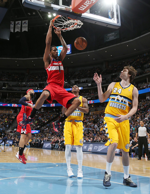 . Washington Wizards forward Trevor Ariza, left, hangs from the rim after dunking as Denver Nuggets forwards Darrell Arthur, center, and Jan Vesely, of the Czech Republic, look on in the first quarter of an NBA basketball game in Denver on Sunday, March 23, 2014. (AP Photo/David Zalubowski)