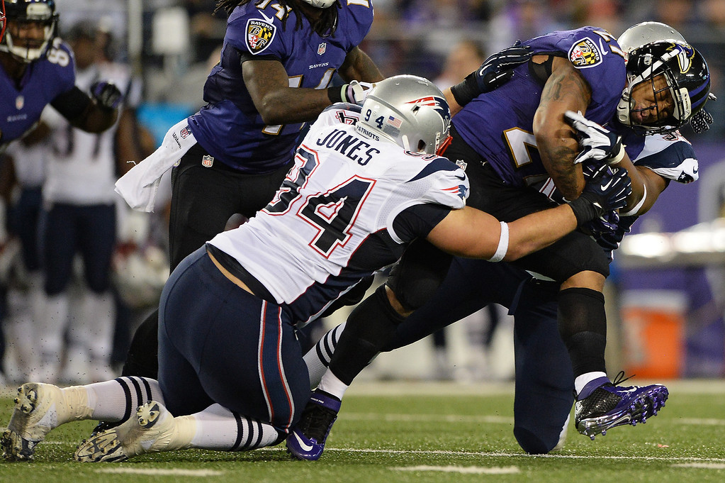 . Running back Ray Rice #27 of the Baltimore Ravens is tackled by defensive tackle Chris Jones #94 of the New England Patriots in third quarter at M&T Bank Stadium on December 22, 2013 in Baltimore, Maryland. The New England Patriots won, 41-7. (Photo by Patrick Smith/Getty Images)
