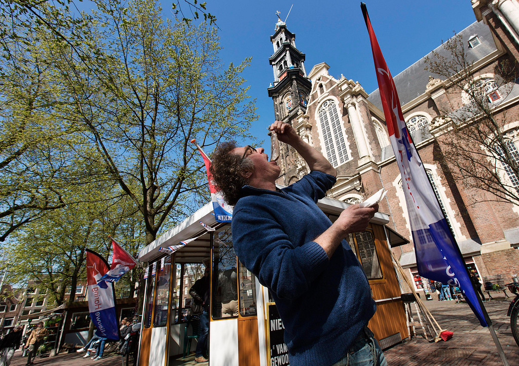 . A man eats a herring the traditional way next to the Westerkerk church in Amsterdam April 24, 2013. The Royal celebrations in the Netherlands this week put the country and the capital Amsterdam on front pages and television screens around the world with an orange splash. There\'s plenty to see and do in 48 hours in this compact city, where the world-famous Rijksmuseum only recently reopened after an extensive renovation. Picture taken April 24, 2013. REUTERS/Michael Kooren