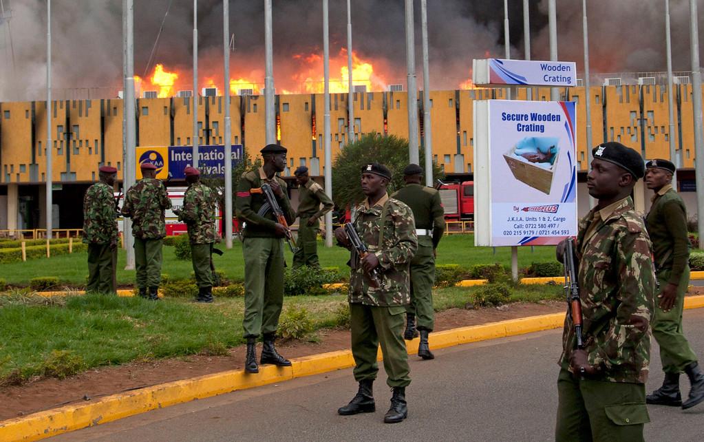 . Armed policemen cordon off the area as fire rages at the international arrivals unit of Jomo Kenyatta International Airport, Nairobi, Kenya, Wednesday, Aug. 7, 2013.  (AP Photo/Sayyid Azim)