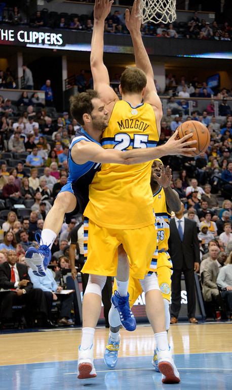 . Dallas Mavericks point guard Jose Calderon (8) makes a pass behind the back of Denver Nuggets center Timofey Mozgov (25)  March 5, 2014 at Pepsi Center. The Denver Nuggets defeated the Dallas Mavericks 115-110. (Photo by John Leyba/The Denver Post)