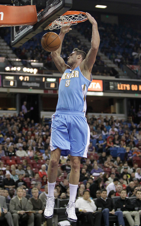 . Denver Nuggets forward Danilo Gallinari, of Italy, hangs on the rim after stuffing against the Sacramento Kings during the first quarter of an NBA basketball game in Sacramento, Calif., Sunday, Dec. 16, 2012.(AP Photo/Rich Pedroncelli)