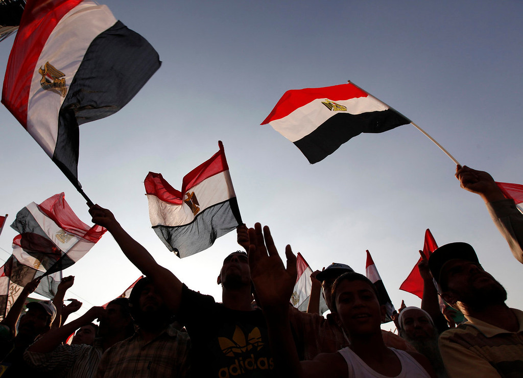 . Members of the Muslim Brotherhood and supporters of Egyptian President Mohamed Mursi shout slogans and wave Egyptian flags during a protest around the Raba El-Adwyia mosque square in Nasr City, in the suburb of Cairo June 29, 2013. Mass demonstrations across Egypt on Sunday may determine its future, two and half years after people power toppled a dictator they called Pharaoh and ushered in a democracy crippled by bitter divisions. The protesters\' goal again is to unseat a president, this time their first freely elected leader, the Islamist Mursi. Liberal leaders say nearly half the voting population - 22 million people - have signed a petition calling for change. REUTERS/Mohamed Abd El Ghany