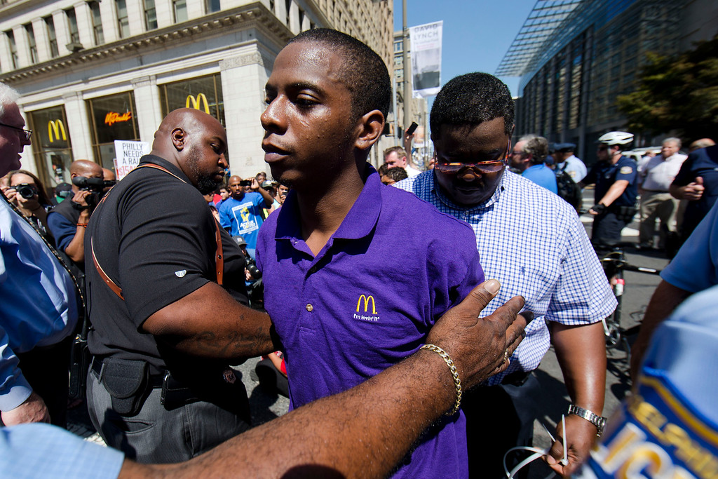 . A McDonald\'s worker is detained by police during a protest to push fast-food chains to pay their employees at least $15 an hour, outside a McDonald\'s restaurant Thursday, Sept. 4, 2014, in Philadelphia. The protest movement, which is backed financially by the Service Employees International Union and others, has gained national attention at a time when the wage gap between the poor and the rich has become a hot political issue. (AP Photo/Matt Rourke)