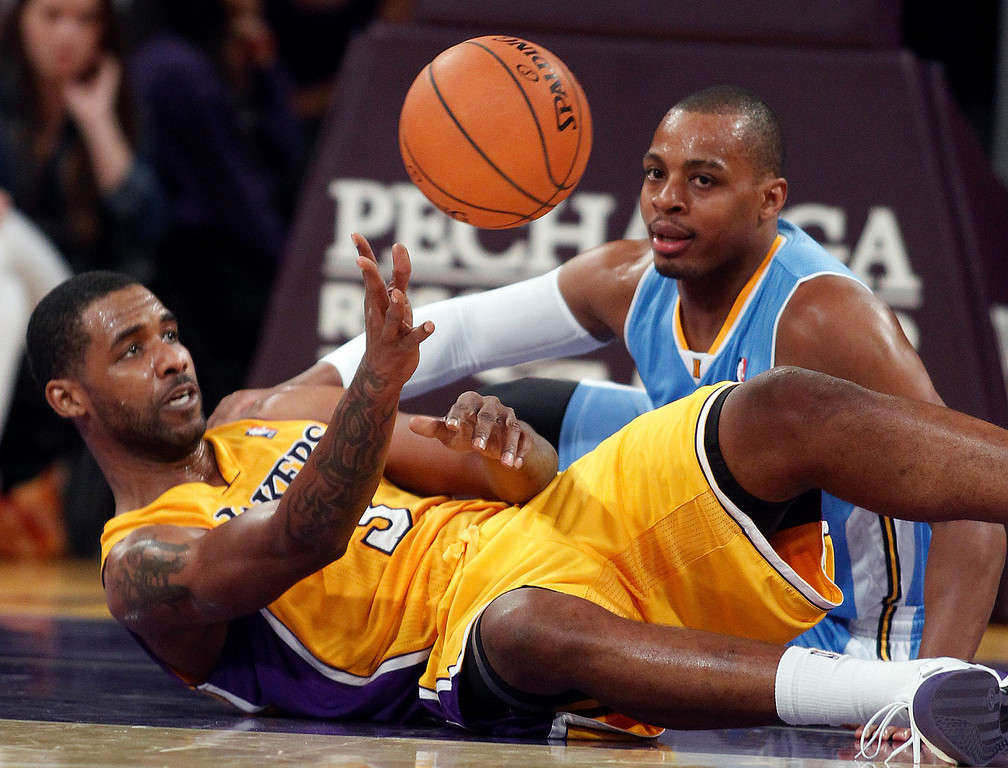 . Los Angeles Lakers forward Shawne Williams, left, passes the ball with Denver Nuggets guard Randy Foye, right, watching in the second quarter during an NBA preseason basketball game Sunday, Oct. 6, 2013 in Los Angeles. (AP Photo/Alex Gallardo)