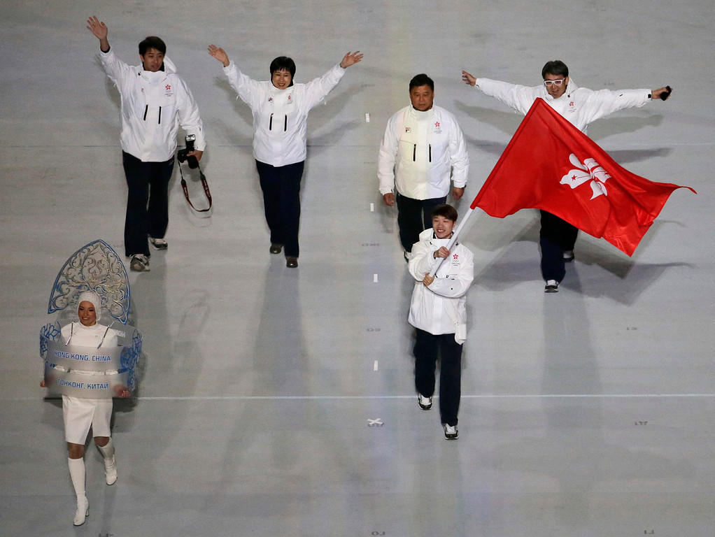 . Lui Pan To Barton of Hong Kong waves his national flag and enters the arena with teammates during the opening ceremony of the 2014 Winter Olympics in Sochi, Russia, Friday, Feb. 7, 2014. (AP Photo/Charlie Riedel)