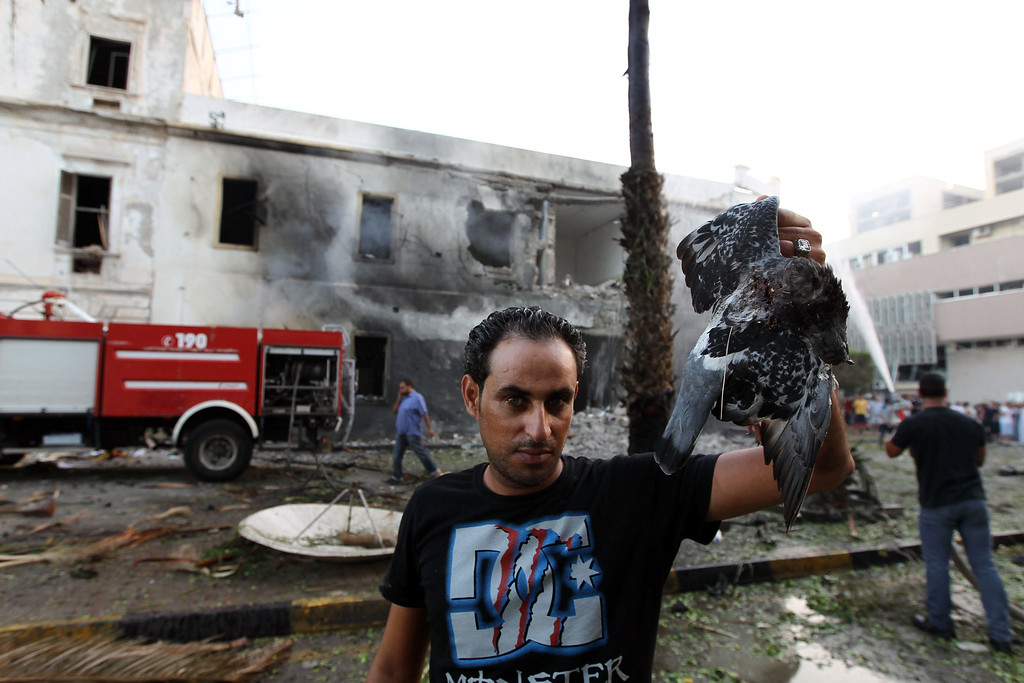 . A Libyan man shows a dead bird in front of firefighters extinguishing a fire caused by a powerful blast near a foreign ministry building on September 11, 2013 in the eastern Libyan city of Benghazi. The explosion comes on the first anniversary of an attack by militants on the United States consulate in Benghazi, which killed four Americans, including the ambassador. ABDULLAH DOMA/AFP/Getty Images