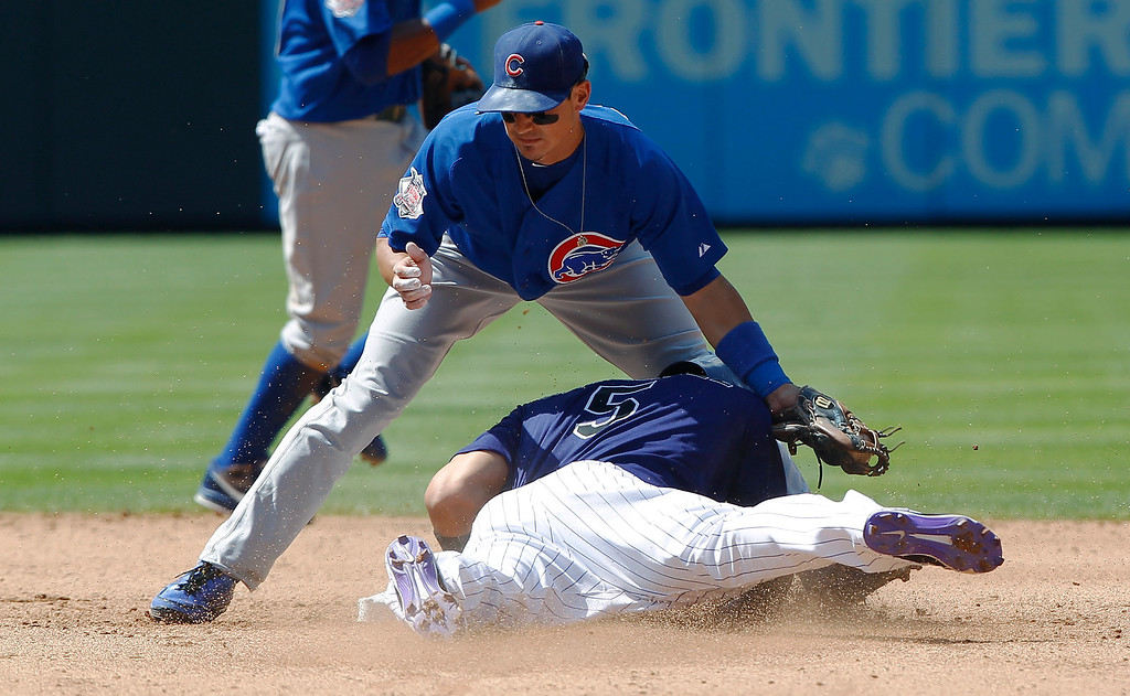 . Chicago Cubs second baseman Darwin Barney, top, applies the late tag to Colorado Rockies\' Carlos Gonalez who steals second base in the fourth inning of a baseball game in Denver, Sunday, July 21, 2013. (AP Photo/David Zalubowski)