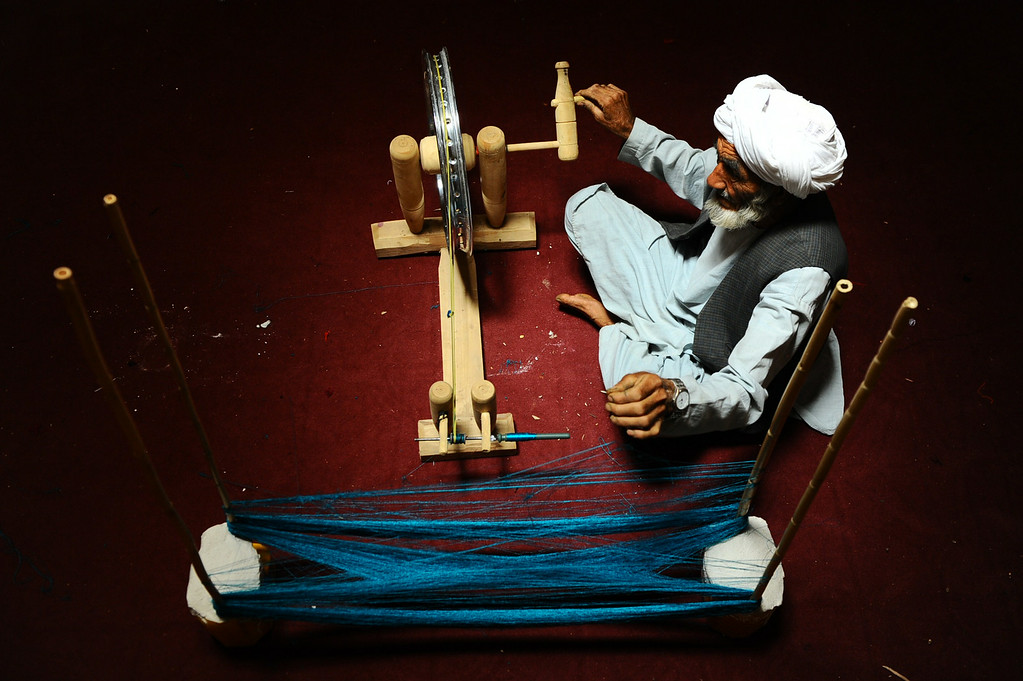 . In this picture taken on June 26, 2014, an Afghan worker weaves threads to be woven into a carpet at a traditional factory in Herat.  AFP PHOTO/Aref Karimi/AFP/Getty Images