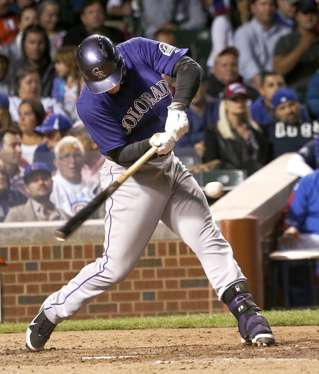 . Colorado Rockies\' Nolan Arenado hits an RBI single off Chicago Cubs starting pitcher Tsuyoshi Wada, scoring Charlie Blackmon, during the sixth inning of a baseball game Monday, July 28, 2014, in Chicago. (AP Photo/Charles Rex Arbogast)