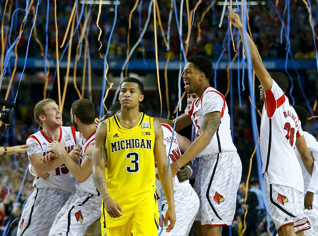 . The Louisville Cardinals celebrate as Michigan Wolverines guard Trey Burke (3) leaves the court after Louisville won the NCAA men\'s Final Four championship basketball game in Atlanta, Georgia April 8, 2013.   REUTERS/Jeff Haynes