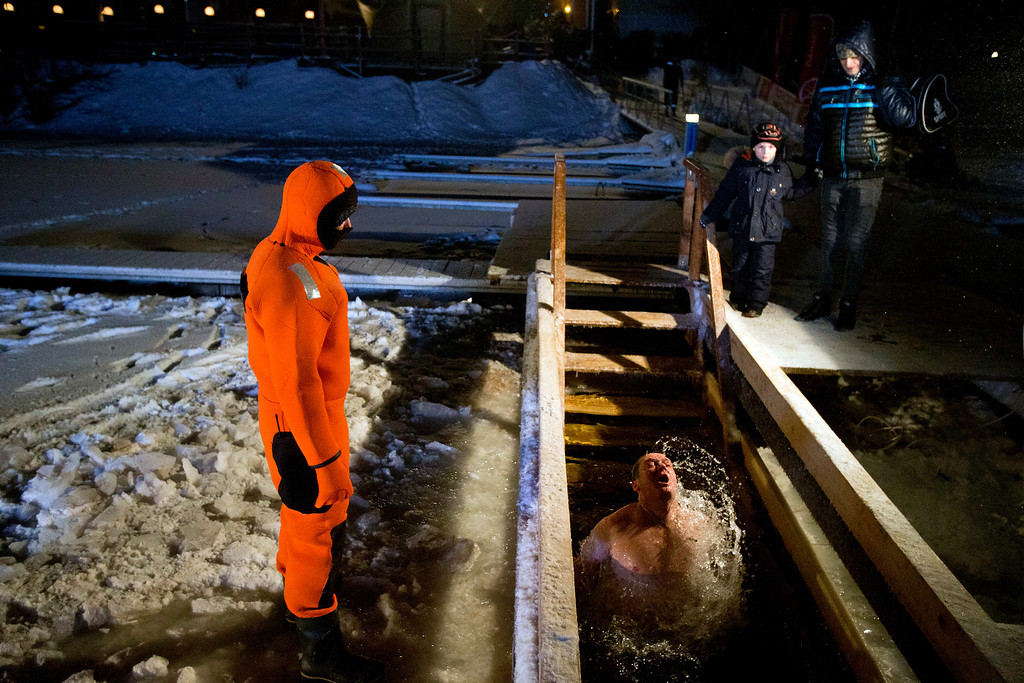 . A Russian man emerges from the icy water on the Moscow river to mark the Epiphany, as a lifeguard looks on, in Moscow, Russia, Saturday, Jan. 18, 2014. The temperature in Moscow is -17C (1.4 F). Thousands of Russian Orthodox Church followers plunged into icy rivers and ponds across the country to mark Epiphany, cleansing themselves with water deemed holy for the day. Water that is blessed by a cleric on Epiphany is considered holy and pure until next year\'s celebration, and is believed to have special powers of protection and healing.  (AP Photo/Pavel Golovkin)
