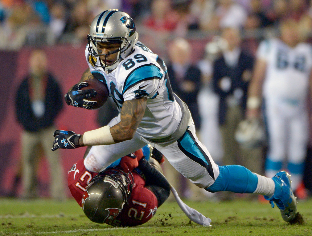 . Carolina Panthers wide receiver Steve Smith (89) is brought down by Tampa Bay Buccaneers defensive back Michael Adams (21) after a reception during the first half of an NFL football game in Tampa, Fla., Thursday, Oct. 24, 2013. (AP Photo/Phelan M. Ebenhack)